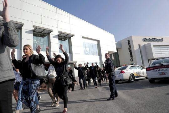 People evacuate after a reported shooting at Fashion Place Mall in Murray, Utah, on Sunday